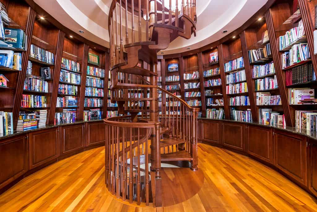 A jaw-dropping home library with circular bookshelves and a very attractive spiral staircase.