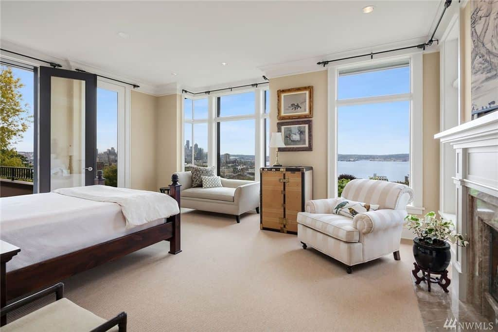 Primary bedroom surrounded with full height glazing that overlooks a magnificent ocean view. It has lounge chairs and a dark wooden bed covered in white bedding.