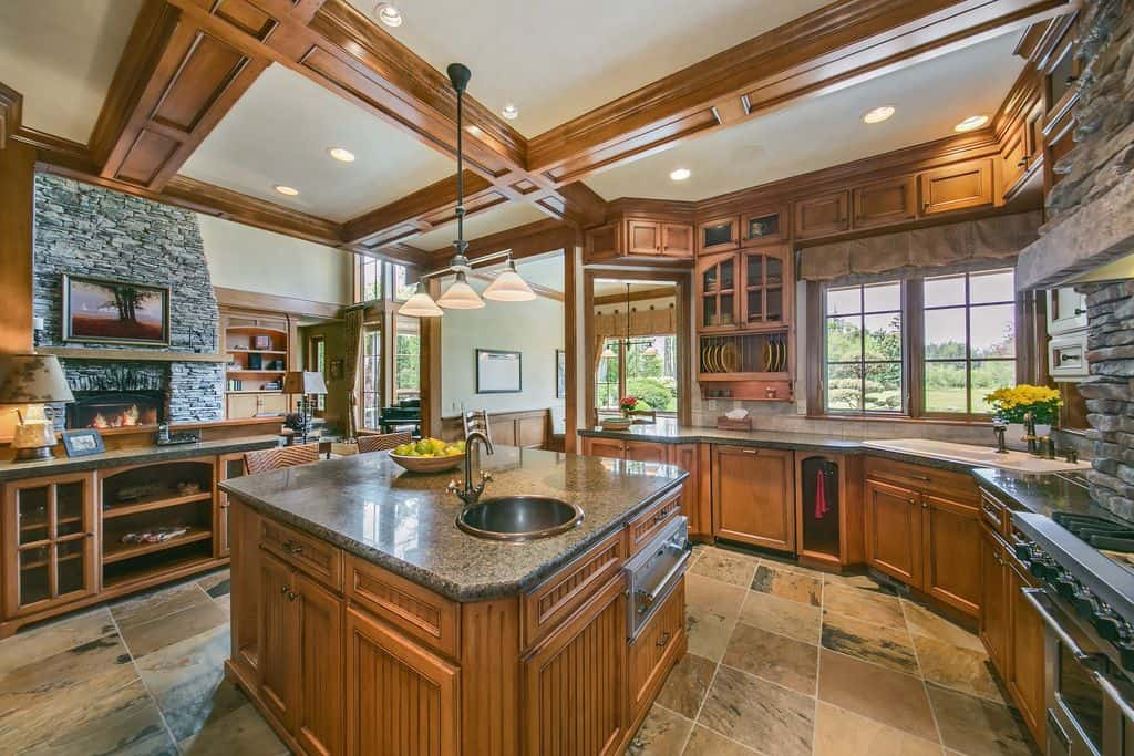 This kitchen offers a center island with a granite countertop set on the tiles flooring lighted by a pendant lighting installed on the ceiling with beams.