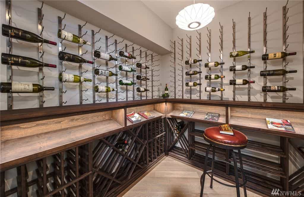 Modern wine room with steel vertical racks above wooden shelves. Beneath it are wooden racks with various patterns. A cushioned stool sits on a hardwood flooring complementing the shelves.