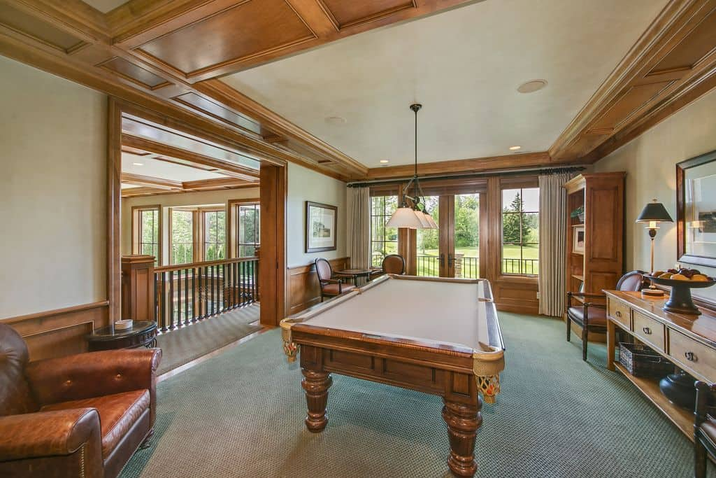 Elegantly-setup game room with a classic billiards pool with beige cloth and is lighted by pendant lights set on the tray ceiling.