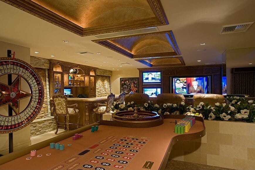 Rustic man cave with stone accent walls flanking the custom western-style bar (saloon style) and face the media area with 4 TVs behind which sites a large gaming table.