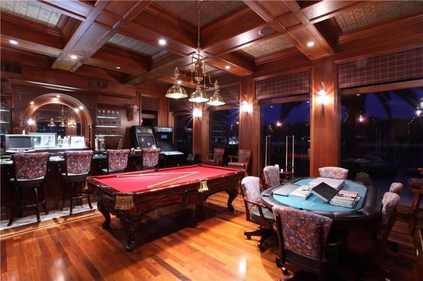 This is a fancy man cave with a huge custom built bar, arcade games, full size red-surface pool table and large oval card table. The room is decked out in extensive custom wood work including gorgeous coffered ceiling with recessed lights built in which illuminate the rich medium dark wood flooring. Wood paneled walls include wall-mounted lights for additional lighting.