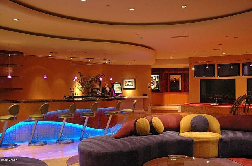 Space age monster man cave in the basement with huge modern bar, curved orange walls, multiple TVs, billiards table and custom sectional sofa with purple, yellow and red color scheme.