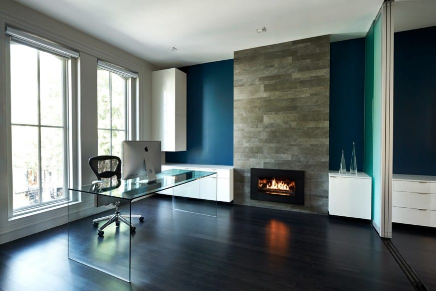 Modern home office with a black fireplace fixed to the stone pillar. It includes a glass table and black office chair over dark hardwood flooring.