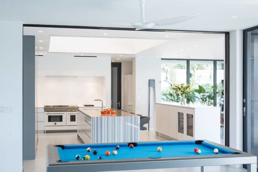An open kitchen features a central kitchen island topped with a striped counter and sink. It has a white dual oven range fixed against the white walls illuminated by recessed ceiling lights.