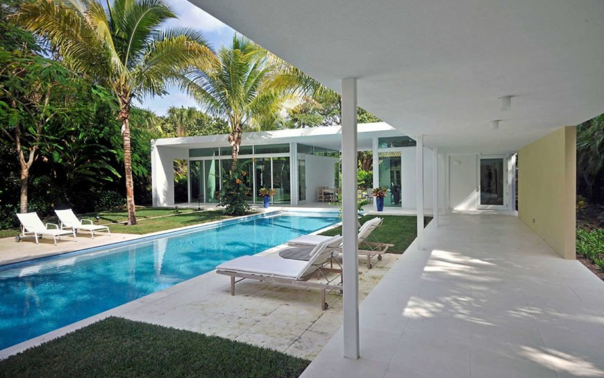 Long rectangular outdoor pool surrounded by tall trees and well-maintained lawn.