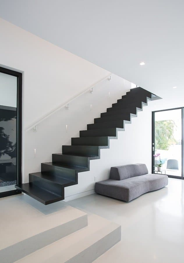 A minimalist entryway filled with a gray velvet couch and black staircase without a railing illuminated by stair lights fixed to the white wall.