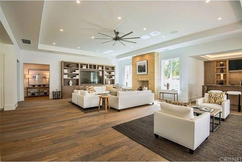 Large great room featuring stylish hardwood flooring and white seats matching the white walls and tray ceiling with scattered recessed lights.