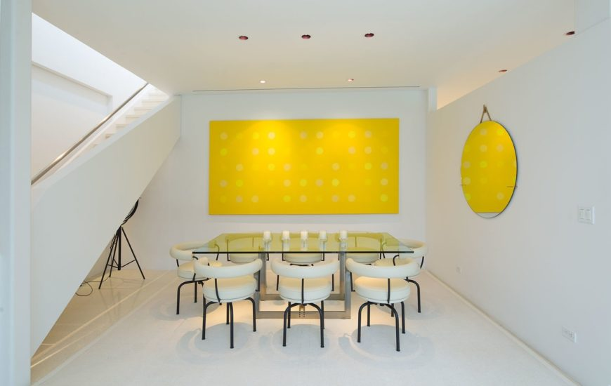 This dining room offers a glass top dining table and modish white chairs surrounded by white walls with yellow wall decors that look so attractive.