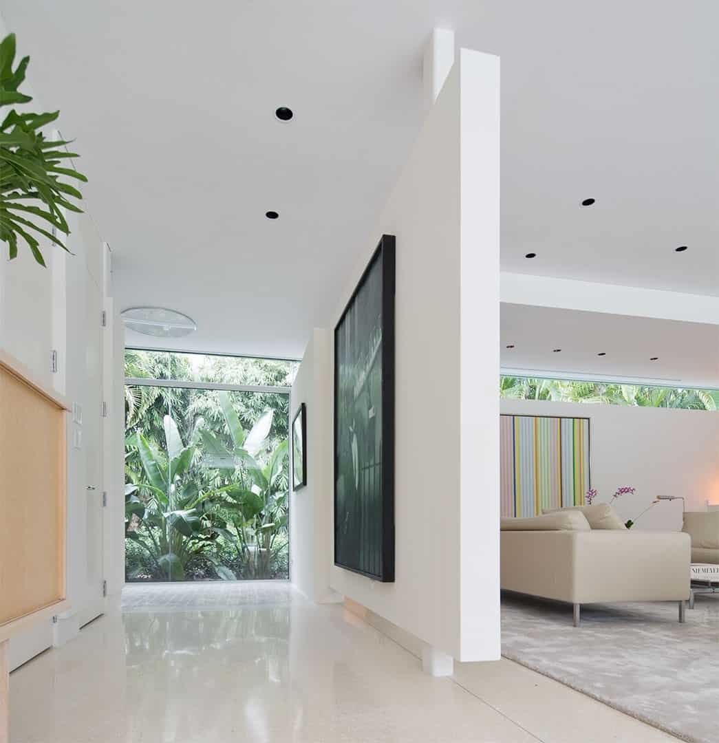 Foyer featuring white walls and flooring along with a massive wall decor. The glass walls and windows overlook the beautiful greenery outside.