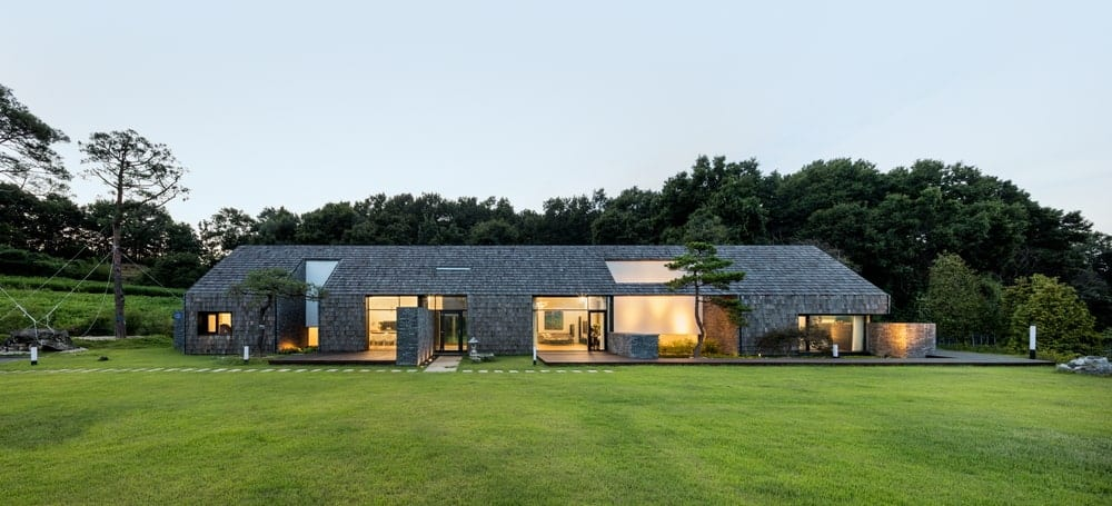 This is a full view of the house's exterior at the back with a large grass lawn, walkways by the Zen garden and large glass walls and doors that glow warmly from the interior lights. These are complemented by the exterior walls of the house that has the same materials on it as the roof.