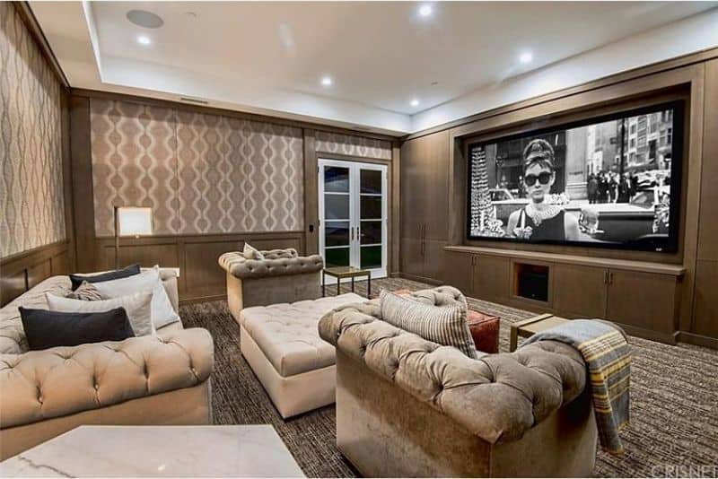 A classy home  theater with elegant seats set on the carpet flooring.