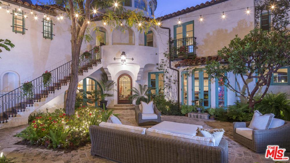 This luxurious home features a classy patio area surrounded by beautiful lighting set on the trees and plants all over the place.