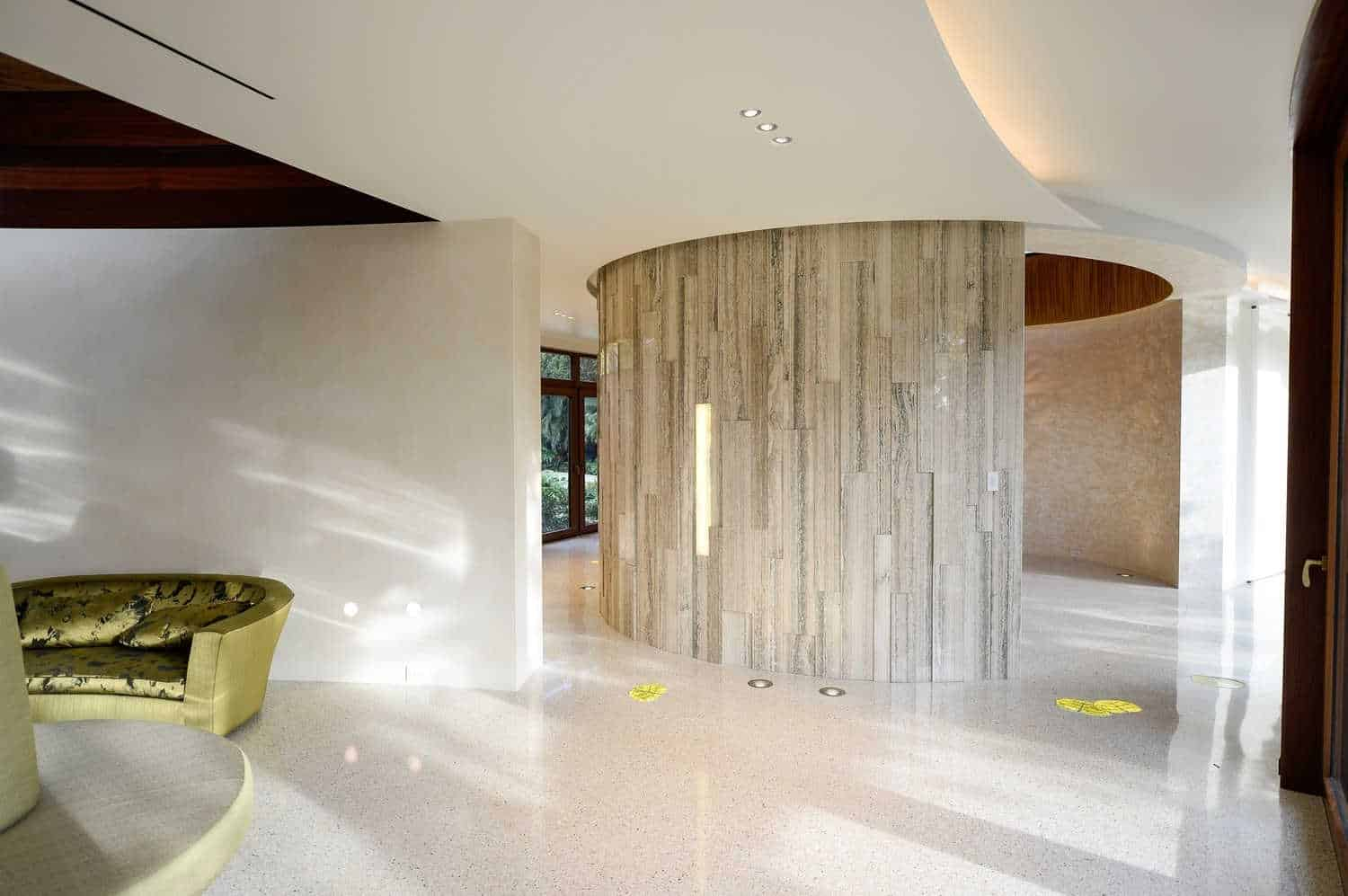 This foyer is surrounded by white walls, flooring and lighted by recessed lights.