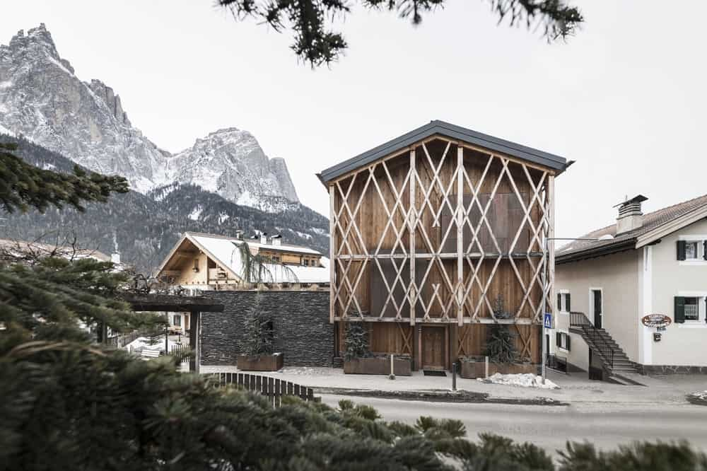 This is an exterior front view of the house with rustic wooden exterior walls adorned by the slats and panels that form geometric patterns that give the facade of the house a unique look..