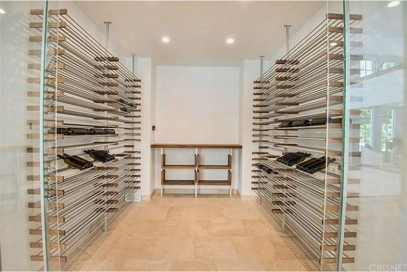 Modern and sleek wine cellar with steel bar racks along with a wooden countertop that serves as the tasting table.