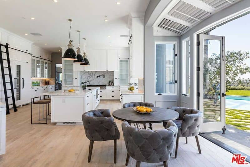 Huge pendant lights hung over a breakfast island with marble countertop and metal stools on this white and stylish kitchen.