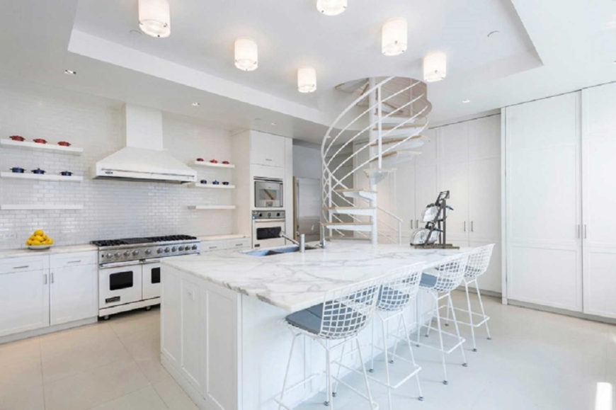 White kitchen area featuring a massive center island with marble countertop, which also serves as a breakfast bar.