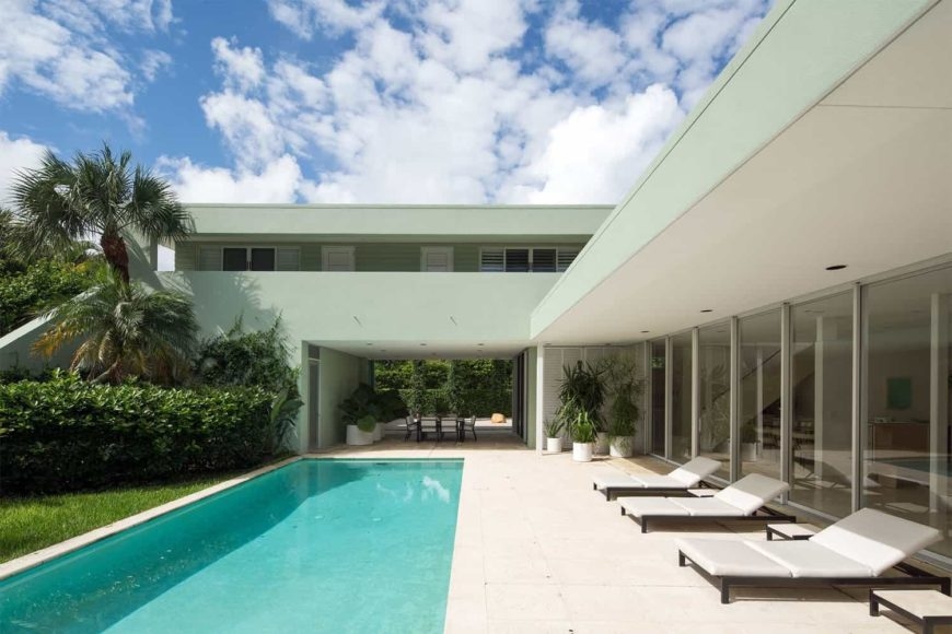 This modern home features a rectangular swimming pool with lounger seats on the side along with a patio area.