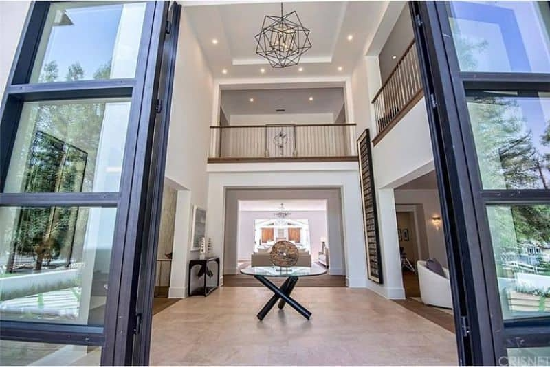 This elegant modern foyer features a tall French doors and a large rug with a center table. The high ceiling is incredible and the lighting is just stunning.