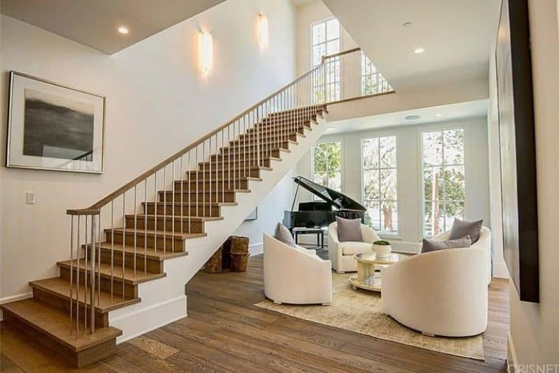 This living area features a round coffee table surrounded with white chairs and accompanied by a baby grand piano beneath the wooden staircase framed with steel railing.