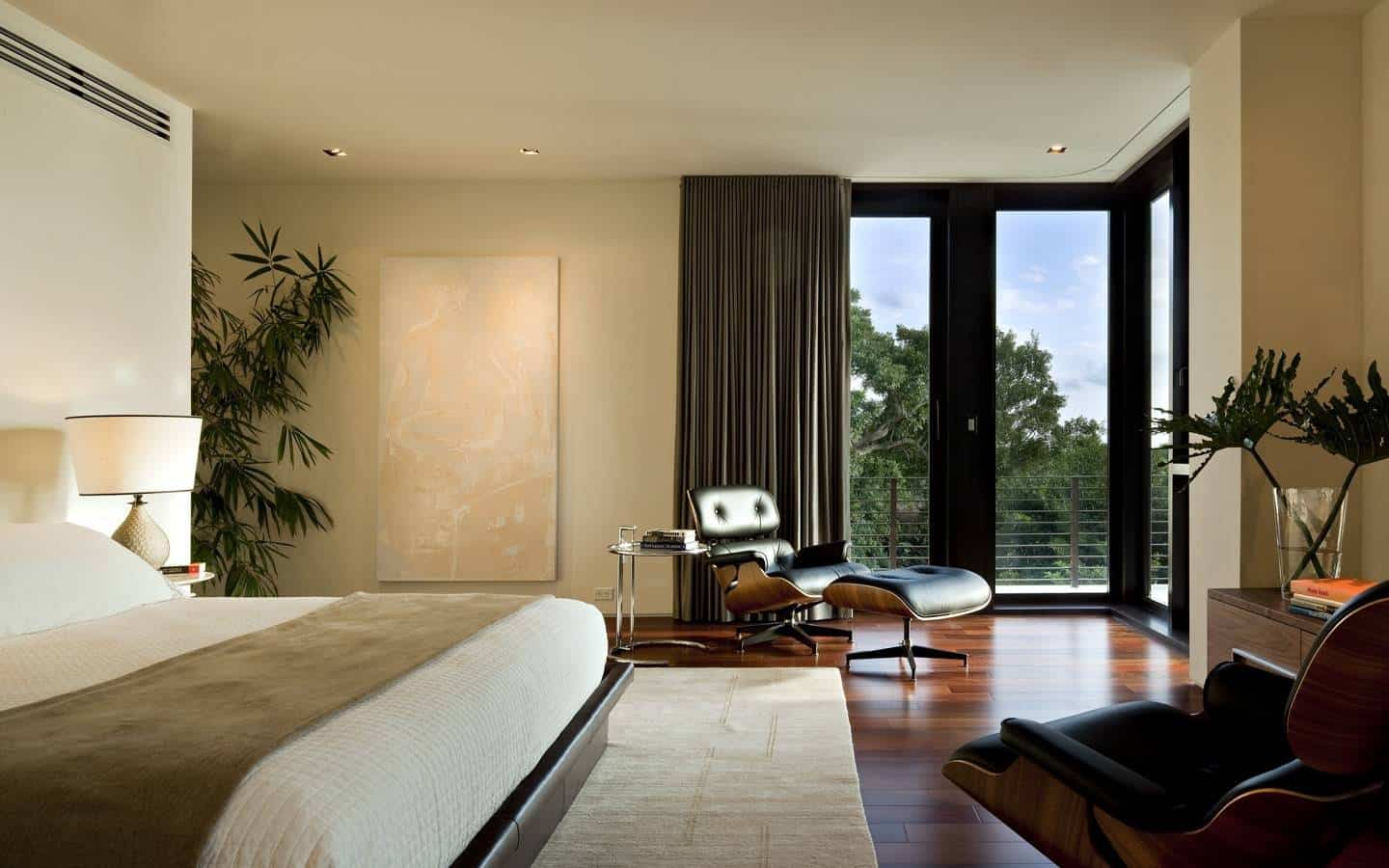 Medium-sized primary bedroom with glass sliding doors, indoor plants, stylish reclining chairs, and hardwood flooring.