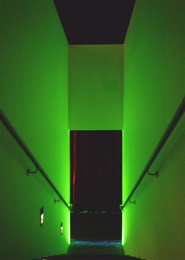 Narrow landing in between illuminated walls with steel handrail.