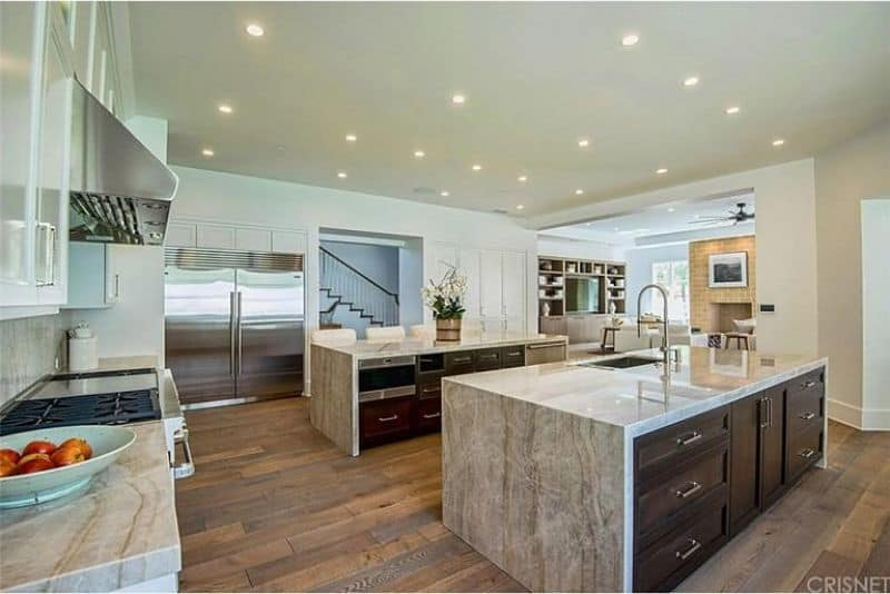 Spacious kitchen with double breakfast islands topped with gray marble which matches the countertop and backsplash is illuminated by scattered recessed lighting.