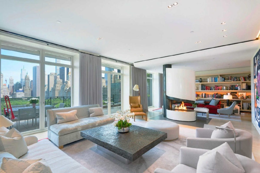 Long and narrow living room offers two sitting areas with a fireplace in the middle that serves as their divider. It has marble flooring and full height windows covered with gray draperies.
