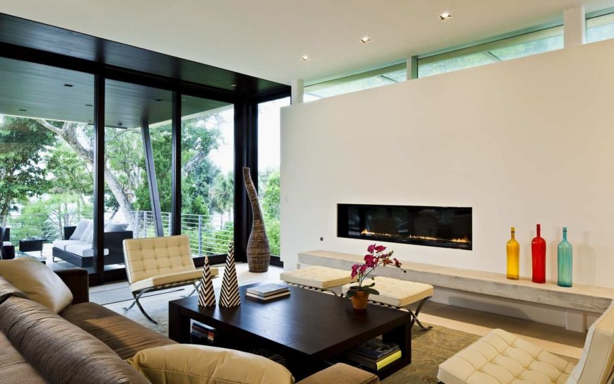 Fresh living room features a comfy sofa and white tufted seats surrounding a dark wood coffee table across the sleek fireplace accented with multicolored bottles.