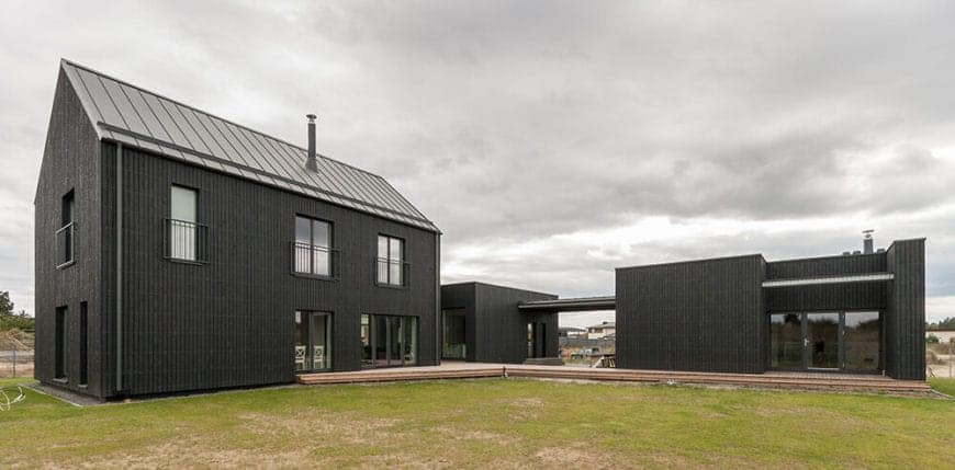 This is Scandinavian-Style house is a wonderful marriage of traditional elements and modern aesthetic. There are three sections of the house connected by a wood-floor exterior that leads to a grassy lawn. Each of the gray-walled sections is complemented by wide windows and glass doors that reflect the cloudy skies.