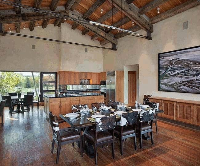 Large kitchen area featuring a dining table set on the hardwood flooring under the stunning ceiling with beams.