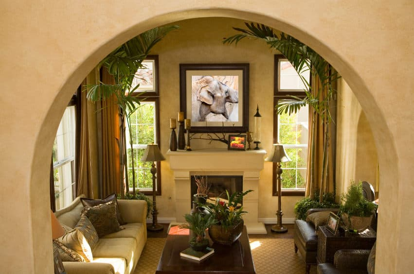 A beige concrete archway opens to a warm living room decorated with a lovely wall art mounted above the fireplace. It has glass windows covered with mustard draperies.