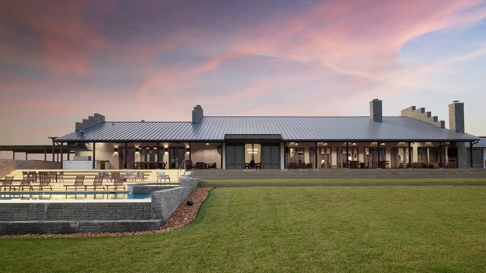 This is an exterior view of the back of the house with multiple glass doors and windows facing a large grass lawn. It has rustic elements and luxury details like the pool area beside the grass lawn.