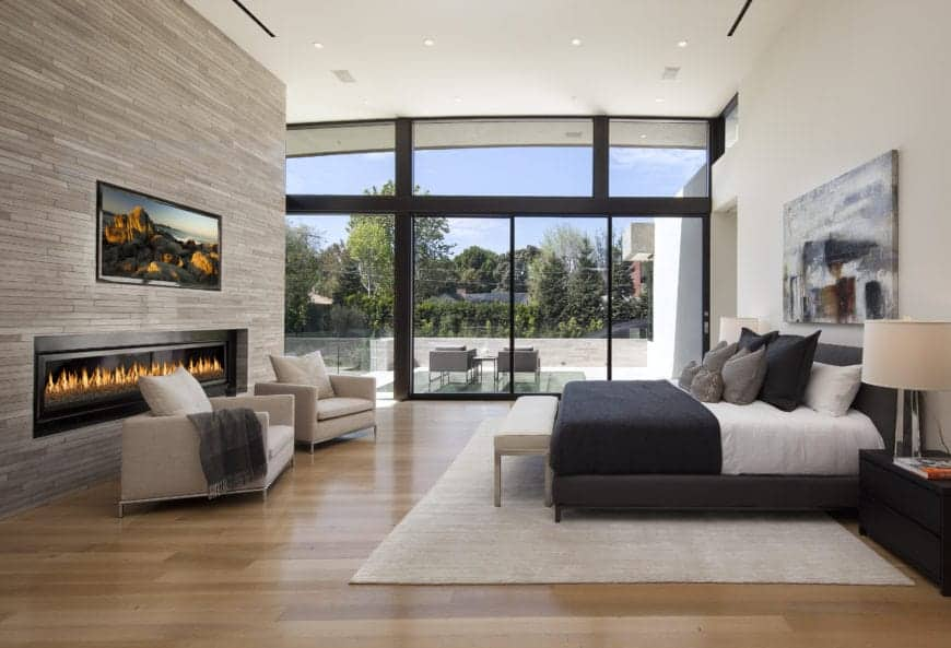 Modern primary bedroom interior with a flat-screen TV above an electric fireplace, a seating area, and sliding glass doors.