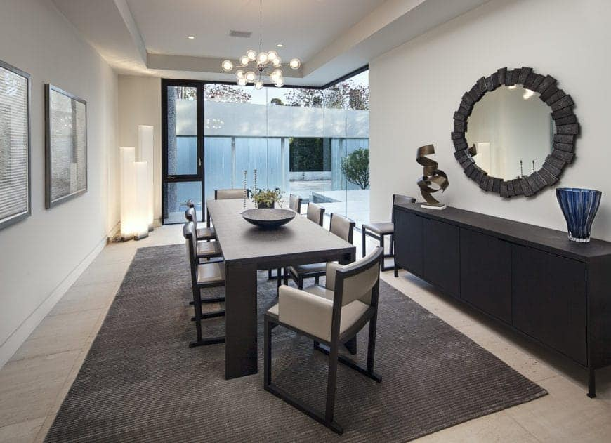 Modern dining room interior with pendant lighting, a round mirror above a side table, a rectangle dining table with eight dining chairs, and an area rug.