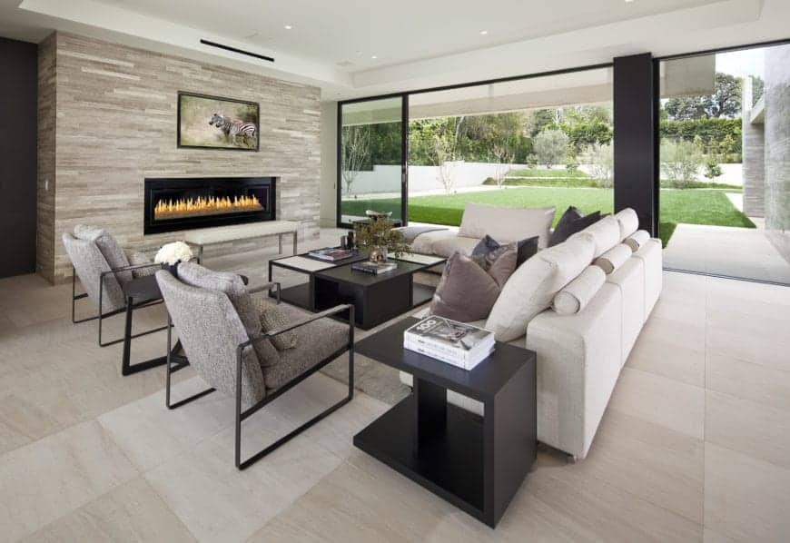 Modern living room interior with a flat-screen TV and electric fireplace, glass sliding doors, and tile flooring.