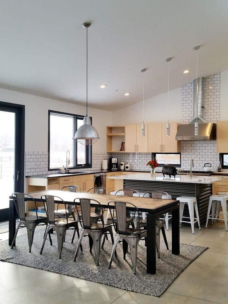 An eat-in kitchen with a rectangle table paired with gray chairs and parallel to the breakfast island. It has concrete flooring topped with a gray rug.