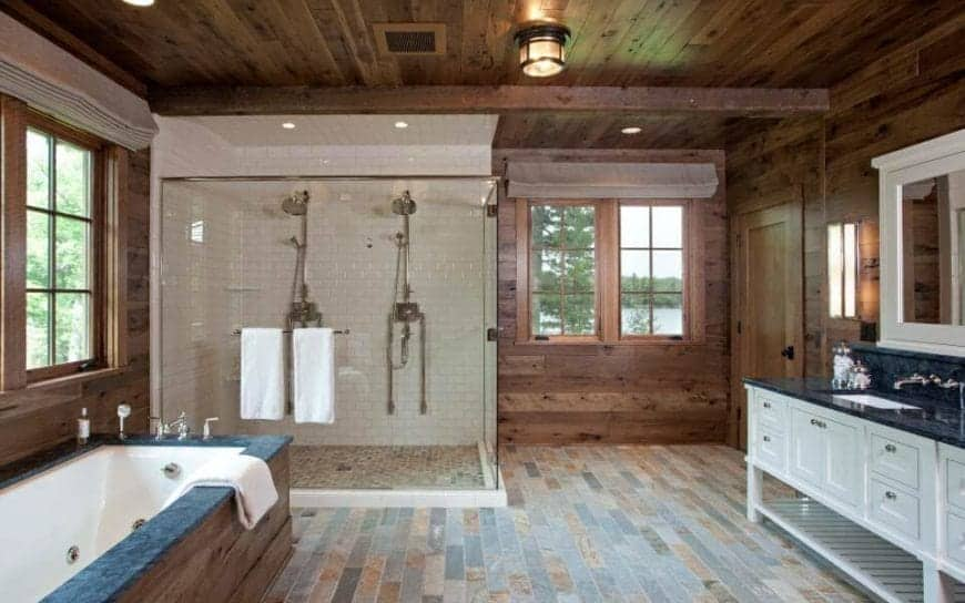This is a Rustic-style primary bathroom with a log cabin feel to its wooden walls and wooden ceiling that has exposed wooden beams. This makes the glass-enclosed shower area stand out with its white tiles covering the walls and ceiling. Next to it is the bathtub embedded with wood that blends with the flooring across from the white wooden vanity.