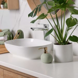 This is a close look at the vanity sink that is paired with a stainless steel faucet.