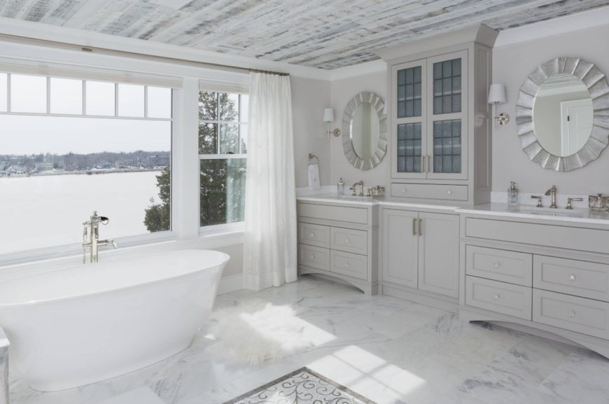 The white freestanding bathtub of this luxurious bathroom is placed by a wide glass window that has a wonderful lakeside view. This brings in natural light on the white marble flooring that is complemented by the large gray wooden structure housing two vanity areas.