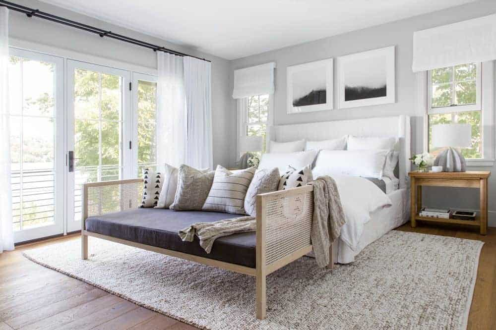 This beautiful bedroom has a bright welcome to the morning with its glass doors bringing in natural lights on the white bed that contrasts the hardwood flooring but complements the gray walls with framed artworks over its white headboard flanked with wooden bedside tables.