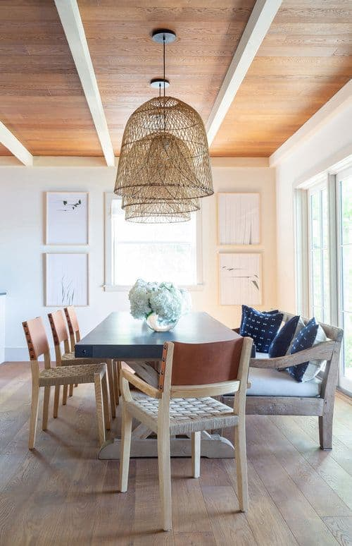 This homey and warm dining room has a hardwood flooring that complements the rustic wooden chairs and wooden cushioned bench surrounding the wooden table that is topped with pendant lights in rustic woven hoods.
