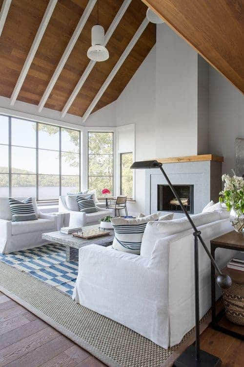 This stunning living room has a wooden cathedral ceiling with white exposed beams matching the white walls that are illuminated by the natural lights coming in from the tall glass windows that brighten the white cushioned sofa set facing a fireplace inlaid into the white walls.