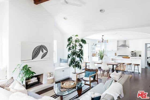 This is a spacious and bright interior complemented by a high cathedral ceiling with an exposed wooden beam. The white walls make this great room shine brighter to contrast the abundance of elements filling the living room, dining room, and kitchen.