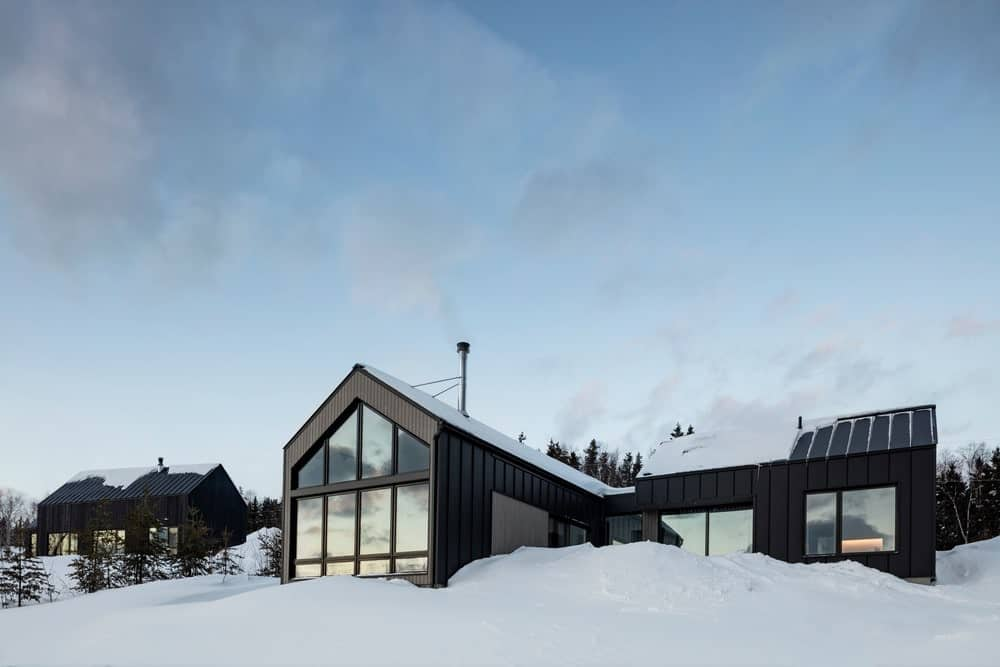 This is a serene view of a Scandinavian-Style L-shaped house against a white background of snow landscape and blue skies that perfectly contrasts the black walls and black Gable roofs. Despite the contrast, this house appreciates the surrounding beauty with massive glass windows.