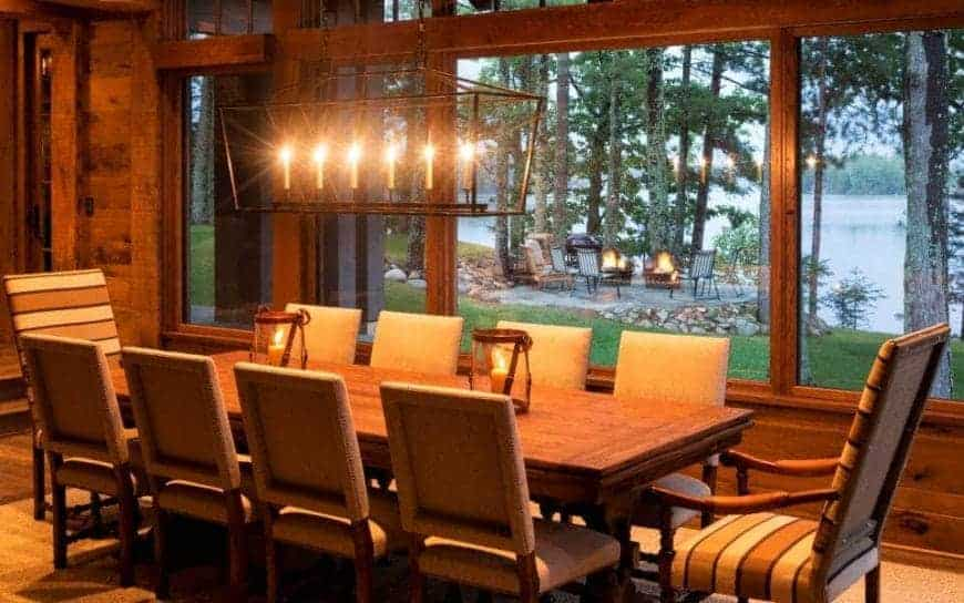 The warm yellow lights that bathe the whole Rustic-style dining room comes from the wrought iron row pendant light hanging over the wooden dining table paired with cushioned chairs. These are all complemented by the lovely lakeside view featured by the wide glass windows.