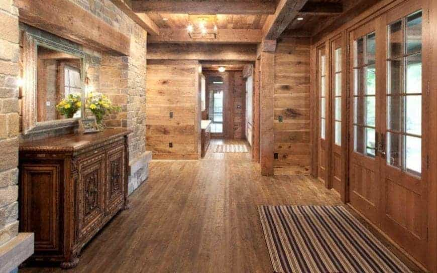 This charming foyer has set of double doors with a wooden finish and framing to its glass panels that brings in an abundance of natural lights to the hardwood flooring, wooden ceiling with exposed beams and the red brick wall across from the entrance.