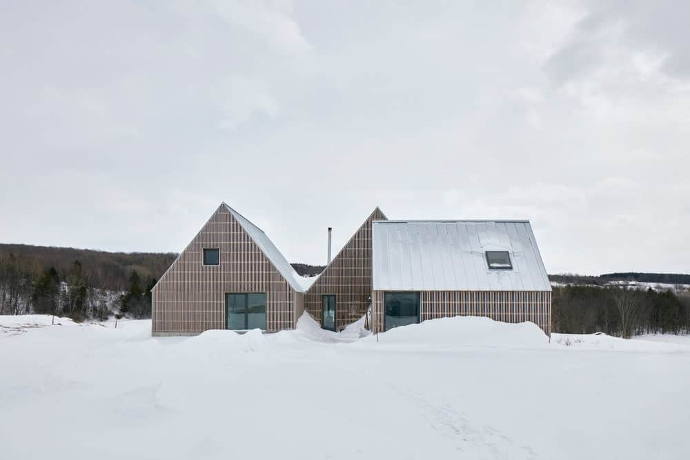 This Scandinavian-Style house has three identical sections with Gable roofs and wooden slat walls paired with wide glass doors. These three sections look like three brothers huddling close to each other in hopes of fighting the cold snow surrounding them.